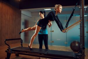 Slim woman and instructor, pilates training